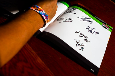 Drivers signing a Lucas Oil Late Model Dirt Series souvenir program