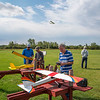210913 Plane Enterprise<br /> James Neiss/staff photographer <br /> Lockport, NY - Flying Weather - Ken Lee flys his RC plane in the background at the Niagara County Model Plane Field on Day Road as enthusiasts Clarence Ragland, Rich Smyth and Carl Cascia work on planes.