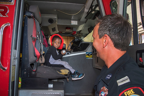 210910 NFFD Enterprise<br /> James Neiss/staff photographer <br /> Niagara Falls, NY - LaSwave Barnes, 2, was all smiles getting a Junior Niagara Falls Firefighter helmet and getting to sit in a truck and hold a microphone under the guidance of Captain Jason Cafarella. Barnes was so excited seeing the truck inside the 10th Street firehouse as he and his parents walked pass, he ran inside to get a better look followed by apologetic parents.