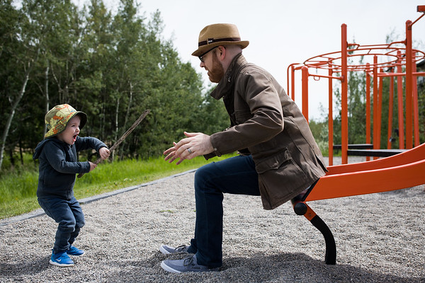 toddler plays with dad on slide