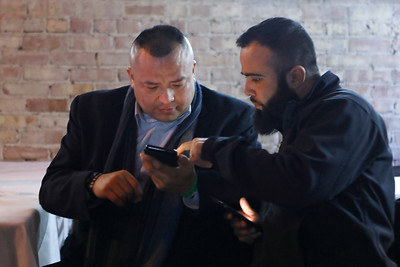 Hercules Gordillo (left) and Cesar Gutierrez (right) check election results on their phones on March 20 at V Bar as they waited for Lisa Hernandez to make an appearance.