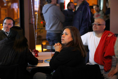 Elizabeth O. Jimenez of Berwyn watches election returns on March 20 as she and fellow Lisa Hernandez volunteers and supporters wait for Hernandez to make an appearance at V Bar.