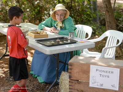 Margaret Hawe shows a child some Pioneer Toys during the 25th annual Days of Living History   at the Gold Nugget Museum in Paradise, Calif. Saturday, Sept. 8, 2018.  (Bill Husa -- Enterprise-Record)