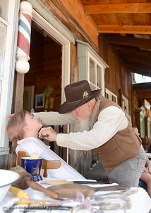 Old time Barber Ken Prentiss gives 8-year-old Andrea Christen of Paradise a fake shave during the 25th annual Days of Living History   at the Gold Nugget Museum in Paradise, Calif. Saturday, Sept. 8, 2018.  (Bill Husa -- Enterprise-Record)