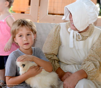 6-year-old Artour Gates of Paradise pets a Silkie chicken with The Coop Boutique Owner Kristen Van Natta during the 25th annual Days of Living History   at the Gold Nugget Museum in Paradise, Calif. Saturday, Sept. 8, 2018.  (Bill Husa -- Enterprise-Record)