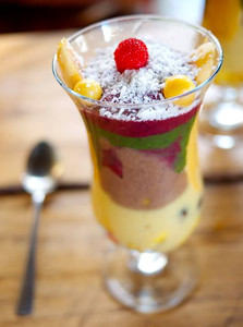 Parfait with different color thick creams blended with a banana-coconut base: mango, mora berry, greens+mint, banana vanilla cream, raw cacao, and a layer of chopped fruit for texture variation. Fragrance comes from mint, coconut, vanilla grown and cured here. Garnish is wild golden berries, raspberry, red banana, and coconut. 90% of ingredients are grown here and picked fresh, retaining vibrant nutrients, color, and flavor. http://VivaLaRaw.org