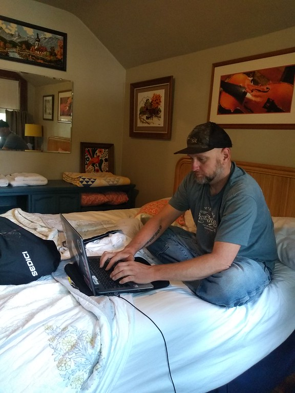 person on bed on laptop writing computer, indoors
