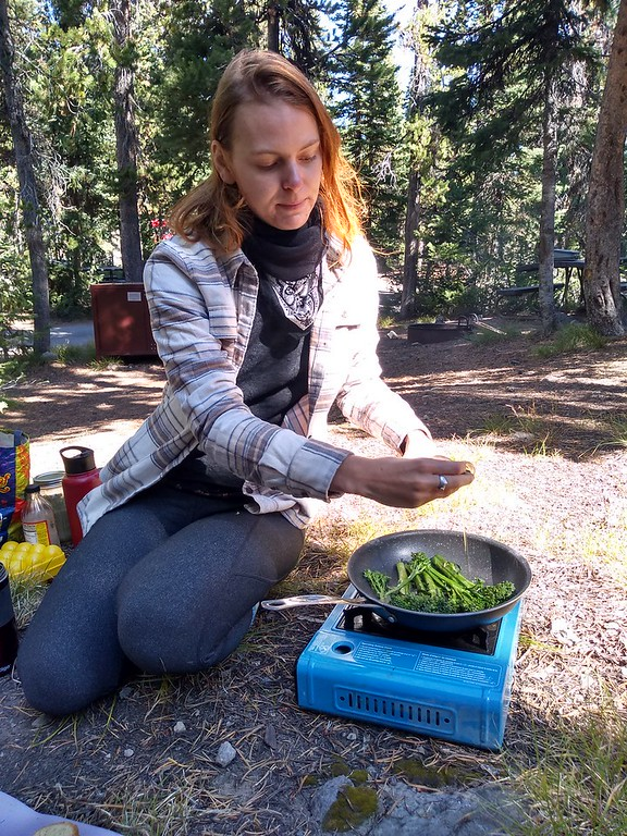 woman cooking on camp stove with pan