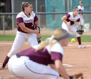 Chico State pitcher Haley Gilham, left, delivers to the plate as thrid baseman Claire Wayne, foreground, and first baseman Olivia Dallara, background, prepare to field the ball as Chico State plays Friday, March 10, 2017, against Cal State Stanislaus in Chico, California. (Dan Reidel -- Enterprise-Record)