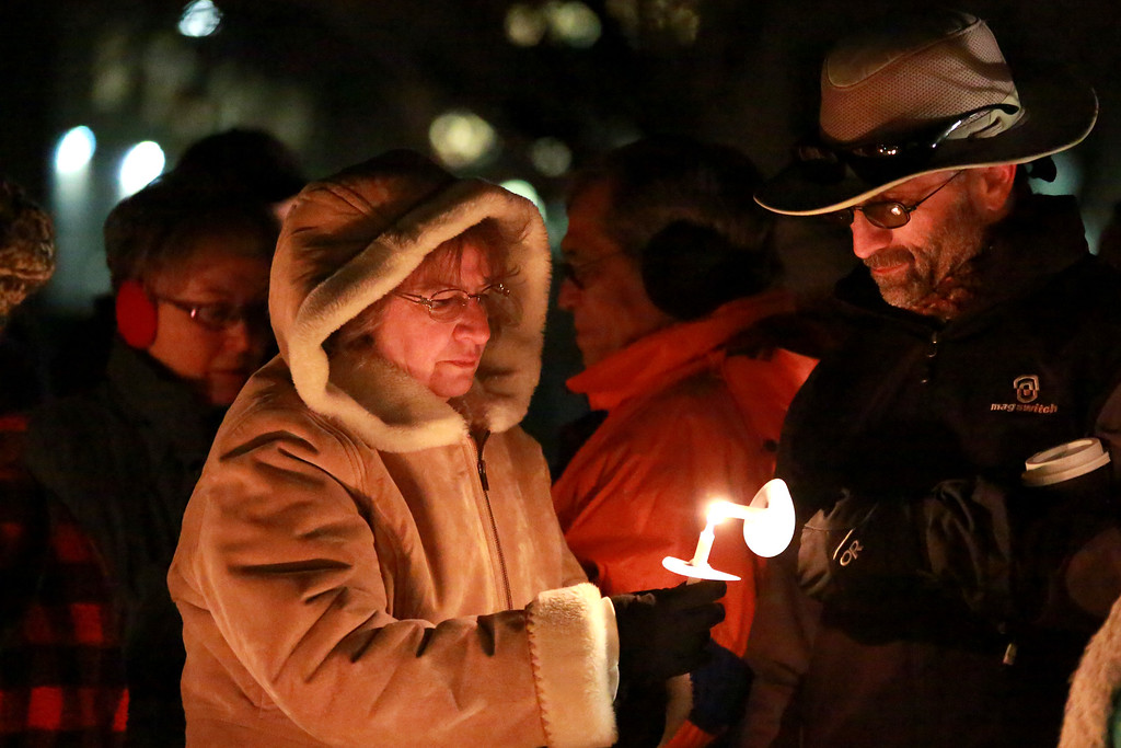 . Pam Montoya lights Neil Brooks� candle at the McKee Angel Statue during the Angel Event hosted by 3 Hopeful Hearts during the vigil for the remembrance of children who have passed away on Dec. 9, 2018 in Loveland, Colo.  Photo by Taelyn Livingston/ Loveland Reporter-Herald