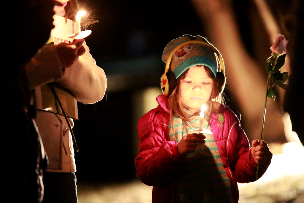 . Emma Greene, 6, holds a candle and a rose at the McKee Angel Statue at the Angel Event hosted by 3 Hopeful Hearts on Dec. 9, 2018 in a vigil for remembrance of children who have passed away in Loveland, Colo.  Photo by Taelyn Livingston/ Loveland Reporter-Herald