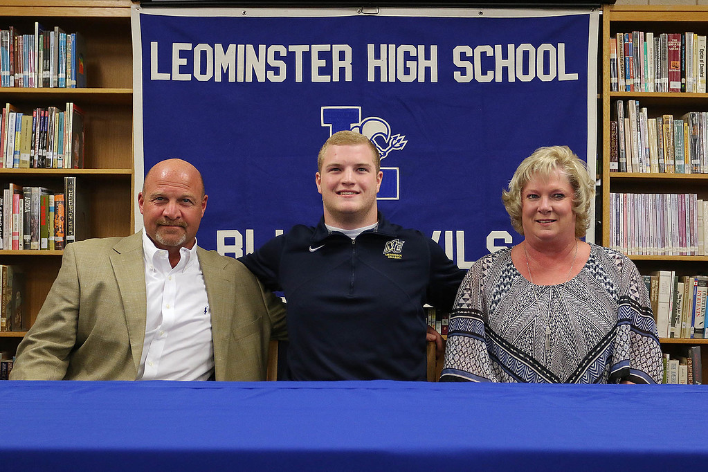 . Anthony Dandini sits with his parents Peter and Christy Dandini at an announcement that he will be headed to Merrimack College in the fall to play football. SENTINEL & ENTERPRISE/JOHN LOVE