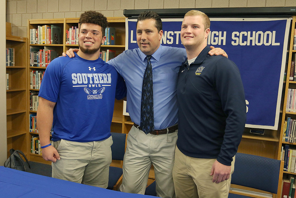 . Leominster High School senior football players Dylan Tanner and Anthony Dandini stand with their football coach Dave Palazzi, center, at an announcement about where they will be playing football next fall. SENTINEL & ENTERPRISE/JOHN LOVE