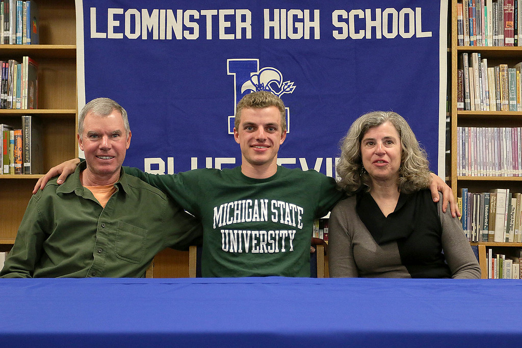 . John Gove sits with his parents Paul and Lisa Gove at an announcement that he will be headed to Michigan State University to run track. SENTINEL & ENTERPRISE/JOHN LOVE