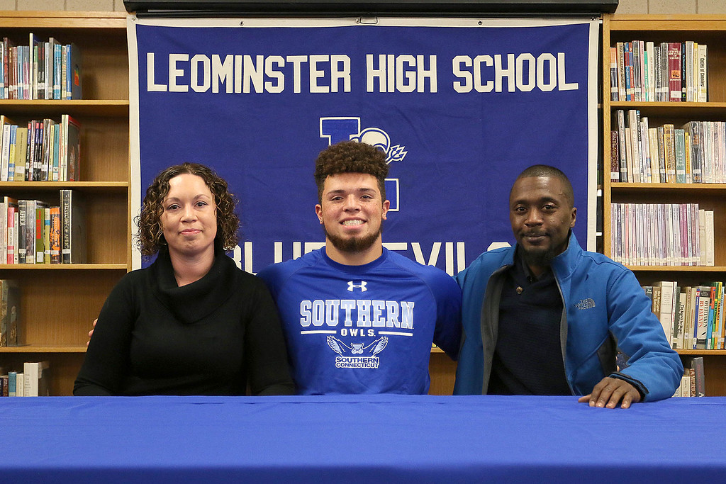 . Leominster High School senior Dylan Tanner sits with his parents Karen Marino and Steve McNamara during a ceremony to announce that he will be playing football at Southern Connecticut State University in the fall. SENTINEL & ENTERPRISE/JOHN LOVE