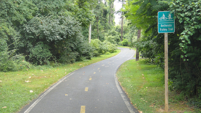 The Bethesda Trolley Trail is a six mile trail stretching from downtown Bethesda, MD to the Twinbrook Metro Station in Rockville. The six mile trail is a variation of off-street shared use paths, on-street bicycle lanes, and sidewalks. The trail crosses many important and busy intersections, but none more so than the crossings over major highways like I-495 and I-270.  <br /> 	<br />      In 1996 TE funding was awarded to two separate projects for the construction of bridges over I-270 and I-495. A total of $1.95 million was awarded and matched by an additional $1.95 million. The construction of these projects was completed in July 2003. The trail has been important for building a trail network in Washington, D.C. because it connects with the Capital Crescent Trail and Rock Creek Trail.<br /> 	<br />      The impact of these trails is profound. From the entrance of one bridge to the entrance on the other side of the highway is a distance of only .2 miles. Without the bridge it would be a 1.3 mile trip to get across I-495. This same is true for the bridge across I-270 except it would be a 1.5 mile trip. This significant investment not only saves time for commuters but also creates an interconnected community where walking and biking are viable options.
