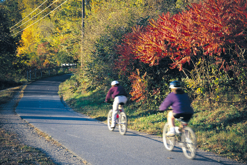 The bikeway during autumn. Photo by Brett Poirier.<br /> <br /> The Burlington Waterfront Bike Path runs for 7.6 miles along the waterfront of Lake Champlain with spectacular views of the Adirondack mountains in New York and the lake itself. Running from the ECHO Lake Aquarium and Science Center to the Winooski River, the trail is used by an estimated 150,000 bikers, pedestrians, joggers, and in-line skaters each year.<br /> <br /> The trail was originally used as a railroad for the Rutland and Burlington Railroad companies, and part of the trail still parallels an active rail line. The railway was used mainly to ship dairy products, but experienced a decline after World War II and was eventually abandoned in 1963. The conversion of the old railroad into a rail-trail began in 1973, and after lengthy battles in the Vermont Supreme Court between the City of Burlington and the railroad companies, the trail was finally completed in 1986. The project received $1,016,000 in TE funding, and the city supplied the additional $254,000 bringing the grand total to $1,270,000.