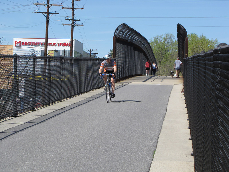 This bridge crossing River Road (MD 190) was a large part of the cost of completing the trail from Bethesda, MD to downtown DC.  It allows pedestrians and cyclists to avoid a challenging at-grade crossing that has no signal.<br /> <br /> The Capital Crescent Trail extends 10.75 miles along the former right-of-way of the Georgetown Branch of the B&O Railroad between Georgetown in Washington, D.C. to Silver Spring in Montgomery County, Maryland. The trail is a recreational and commuting resource connecting residential, commercial, and employment centers. Along its route, the trail passes over four historic bridges, through two historic tunnels, and provides beautiful vistas of the Potomac River. The transformation from a disused single-track rail line to a first-class trail is an impressive example of cooperation between civic groups and governments. A coalition - comprised of community, environmental, outdoors-oriented groups, and individual citizens - worked with federal, state, county, and district governments to make the trail happen. The 6.4-mile portion of the trail in Maryland received $1.15 million in Transportation Enhancements funding in addition to $6.33 million in local, state, private funding and donations. Congress appropriated $11.5 million for the National Park Service to acquire and develop the 4.3- mile portion of the trail in D.C.
