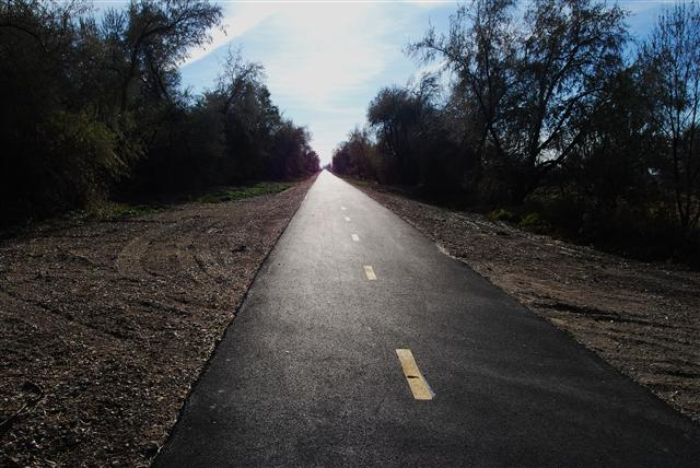 """<a href=""""http://www.UtahOutdoorSports.com/""""> Photo Credit: Willam Barba – UtahOutdoorSports.com<a/>  The Denver and Rio Grande Western Rail Trail extends from Farmington Bay Bird Refuge, where it joins the Legacy Parkway Trail, and runs north through Layton to 4800 S St. near West Park in Clinton. Beyond that the trail continues to Hinckley Drive in Roy. The trail continues to Clearfield and terminates in Roy.   The abandoned right-of-way is owned by the Utah Transit Authority in a land bank for future transportation needs. The various cities it links with have agreements with the light- and commuter-rail agency to maintain the trail.  Since 2006, four separate Transportation Enhancement awards focused on building the Denver and Rio Grande Western Rail Trail. In total, $1.28 million was invested through TE with an additional $320,000 coming from local sources for a total of approximately $1.6 million. The trail is 23.7 miles long and offers connections to the Legacy Trail and the Jordan Parkway Trail."""