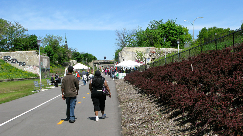 """The southernmost portion of the trail passes through a dense residential area, providing access to the riverfront and Detroit's <a href=""""http://www.detroiteasternmarket.com/"""">Eastern Market</a>.  The Dequindre Cut is a 1.2 mile rail-trail that connects the Detroit waterfront to several residential and commercial areas. This project converted an abandoned, derelict railroad corridor into a greenway, preserving the right-of-way for transportation use and creating a valuable amenity for the city and for travelers. A $2 million federal TE award in 2004 leveraged a local match of over half a million dollars to construct the first segment of the trail. The full right-of-way is over four miles long, and an extension to the first segment is already under construction."""