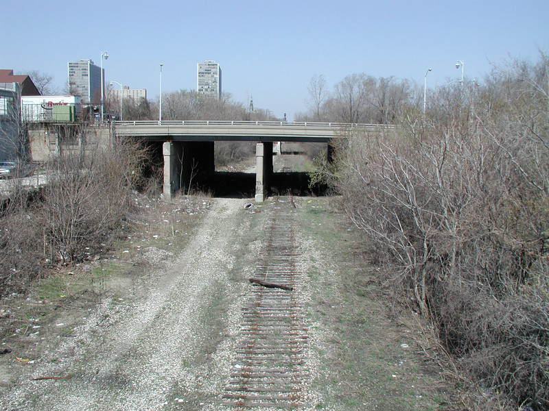 This image is from the southern end of the first segment of the trail, prior to trail development.<br /> <br /> The Dequindre Cut is a 1.2 mile rail-trail that connects the Detroit waterfront to several residential and commercial areas. This project converted an abandoned, derelict railroad corridor into a greenway, preserving the right-of-way for transportation use and creating a valuable amenity for the city and for travelers. A $2 million federal TE award in 2004 leveraged a local match of over half a million dollars to construct the first segment of the trail. The full right-of-way is over four miles long, and an extension to the first segment is already under construction.