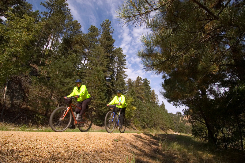 """Photo by  <a href=""""http://www.travelsd.com"""">http://www.travelsd.com</a><br /> <br /> This 114-mile rail-trail, named in honor of former Governor Mickelson, passes through the heart of South Dakota's Black Hills. The trail's 100 converted railroad bridges and 4 rock tunnels accommodate hikers, horseback riders, bicyclists, an annual Mickelson Trail Bike Trek, cross-country skiers and along some portions of the trail, snowmobilers. Visitors and residents alike use the trail for travel between area towns. The $5.5 million project has received almost $2 million in TE funds, encouraged the opening of trail-related businesses, and spurred historic preservation in the towns the trail travels through.  The trail runs from Deadwood, the town where Wild Bill Hickok was shot and killed, to Edgemont.  Along the way, trail users experience the dense pine forests, rocky canyons, native prairie, high desert, twisting creeks, and numerous wildlife-spotting opportunities of the Wild West."""