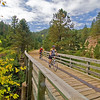 "Photo by  <a href=""http://www.travelsd.com"">http://www.travelsd.com</a><br /> <br /> This 114-mile rail-trail, named in honor of former Governor Mickelson, passes through the heart of South Dakota's Black Hills. The trail's 100 converted railroad bridges and 4 rock tunnels accommodate hikers, horseback riders, bicyclists, an annual Mickelson Trail Bike Trek, cross-country skiers and along some portions of the trail, snowmobilers. Visitors and residents alike use the trail for travel between area towns. The $5.5 million project has received almost $2 million in TE funds, encouraged the opening of trail-related businesses, and spurred historic preservation in the towns the trail travels through.  The trail runs from Deadwood, the town where Wild Bill Hickok was shot and killed, to Edgemont.  Along the way, trail users experience the dense pine forests, rocky canyons, native prairie, high desert, twisting creeks, and numerous wildlife-spotting opportunities of the Wild West."