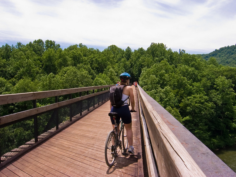 """<a href=""""http://www.flickr.com/photos/jasonpratt/"""">Photo Credit</a>  Biking over the Youghiogheny  With 100 continuous miles of trail open in Pennsylvania from McKeesport to Meyersdale and an additional twenty miles scattered throughout the Pittsburgh area, the <a href=""""http://www.atatrail.org/"""">Great Allegheny Passage</a> is the longest multi-purpose rail-trail in the East. The rail-trail offers a total of 150 miles of non-motorized, nearly level trail between Cumberland, Maryland and Pittsburgh, Pennsylvania with a 52-mile spur to Pittsburgh International Airport. At Cumberland, the Passage will link with the Chesapeake & Ohio Canal Towpath, creating a 300-mile off-road route between Pittsburgh and Washington, DC. The Great Allegheny Passage allows hikers, bicyclists, cross-country skiers and people with disabilities the opportunity to discover the region's spectacular river gorges, mountain vistas and sweeping cityscapes. The Passage leads travelers through the Allegheny Mountains making use of refurbished railroad bridges and tunnels on their journey along waterways, unique rock formations, and wildlife areas. The trail was completed with the help of a $4 million TE grant. A public-private partnership between the Pennsylvania Department of Transportation and the <a href=""""http://www.atatrail.org/"""">Allegheny Trail Alliance</a> (a coalition of seven trail organizations in Southwestern Pennsylvania and Western Maryland), manages this comprehensive project and has significantly contributed to the project's success."""