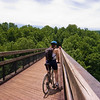 "<a href=""http://www.flickr.com/photos/jasonpratt/"">Photo Credit</a>  Biking over the Youghiogheny  With 100 continuous miles of trail open in Pennsylvania from McKeesport to Meyersdale and an additional twenty miles scattered throughout the Pittsburgh area, the <a href=""http://www.atatrail.org/"">Great Allegheny Passage</a> is the longest multi-purpose rail-trail in the East. The rail-trail offers a total of 150 miles of non-motorized, nearly level trail between Cumberland, Maryland and Pittsburgh, Pennsylvania with a 52-mile spur to Pittsburgh International Airport. At Cumberland, the Passage will link with the Chesapeake & Ohio Canal Towpath, creating a 300-mile off-road route between Pittsburgh and Washington, DC. The Great Allegheny Passage allows hikers, bicyclists, cross-country skiers and people with disabilities the opportunity to discover the region's spectacular river gorges, mountain vistas and sweeping cityscapes. The Passage leads travelers through the Allegheny Mountains making use of refurbished railroad bridges and tunnels on their journey along waterways, unique rock formations, and wildlife areas. The trail was completed with the help of a $4 million TE grant. A public-private partnership between the Pennsylvania Department of Transportation and the <a href=""http://www.atatrail.org/"">Allegheny Trail Alliance</a> (a coalition of seven trail organizations in Southwestern Pennsylvania and Western Maryland), manages this comprehensive project and has significantly contributed to the project's success."