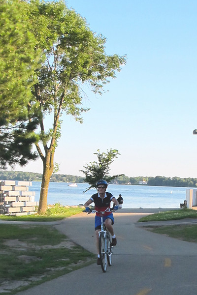 "<b>The Greenbush Link provides connections to trails along the Lake Monona and Monona Bay. </b>  The ""Greenbush Link"" is a 1-mile segment of the Southwest Path in Madison, Wisconsin (Dane County). The Southwest Path is 5.6 miles in length and is the northern reach of the Badger State Trail, a 40-mile trail that connects Madison to Freeport, Illinois.   In 2002, Wisconsin Department of Transportation awarded the City of Madison a $1.46 million TE grant to construct the Greenbush Link portion of the trail, which had become known as the ""missing link."" Completion of this ""missing link"" in 2006 closed the 18-mile loop around central Madison and along the Nine Springs E-Way. It also connects the Southwest Commuter Path with the Isthmus Bike Path and the Capital City Trail as well as regional trails such as the Military Ridge State Trail.   This 1-mile corridor in downtown Madison was very difficult for the Madison Department of Transportation to assemble due to physical constraints and property ownership challenges. Ultimately, the city pieced together a corridor that involves rails-with-trails, easements from the University of Wisconsin and private properties, renegotiation of leases with three commercial property owners, two new crossings of active rail line, and other miscellaneous property agreements. Extensive retaining walls built as well as a new bridge over an arterial street were constructed. The total cost of the construction was approximately $3 million. Land costs added approximately $400,000 to the final price tag."