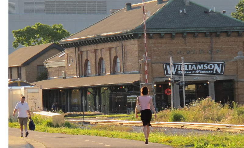 """<b>Williamson Bikes and Fitness, housed in a renovated train depot, is located adjacent to the Greenbush Link.</b>  The """"Greenbush Link"""" is a 1-mile segment of the Southwest Path in Madison, Wisconsin (Dane County). The Southwest Path is 5.6 miles in length and is the northern reach of the Badger State Trail, a 40-mile trail that connects Madison to Freeport, Illinois.   In 2002, Wisconsin Department of Transportation awarded the City of Madison a $1.46 million TE grant to construct the Greenbush Link portion of the trail, which had become known as the """"missing link."""" Completion of this """"missing link"""" in 2006 closed the 18-mile loop around central Madison and along the Nine Springs E-Way. It also connects the Southwest Commuter Path with the Isthmus Bike Path and the Capital City Trail as well as regional trails such as the Military Ridge State Trail.   This 1-mile corridor in downtown Madison was very difficult for the Madison Department of Transportation to assemble due to physical constraints and property ownership challenges. Ultimately, the city pieced together a corridor that involves rails-with-trails, easements from the University of Wisconsin and private properties, renegotiation of leases with three commercial property owners, two new crossings of active rail line, and other miscellaneous property agreements. Extensive retaining walls built as well as a new bridge over an arterial street were constructed. The total cost of the construction was approximately $3 million. Land costs added approximately $400,000 to the final price tag."""