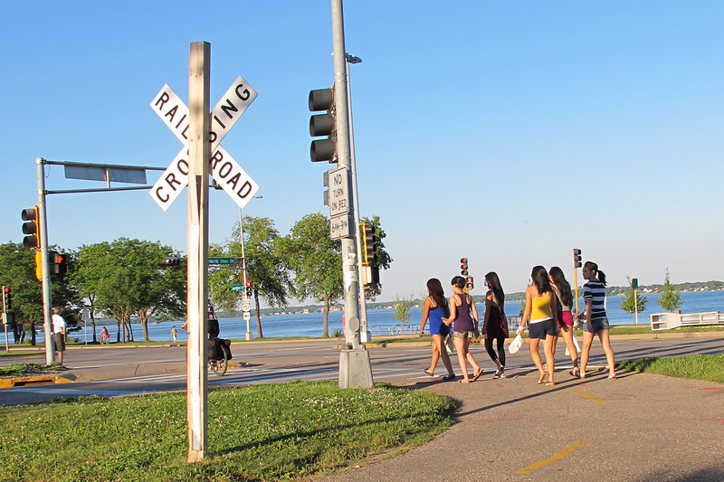 """<b>The Greenbush Link provides connections to trails along the Lake Monona and Monona Bay. </b>  The """"Greenbush Link"""" is a 1-mile segment of the Southwest Path in Madison, Wisconsin (Dane County). The Southwest Path is 5.6 miles in length and is the northern reach of the Badger State Trail, a 40-mile trail that connects Madison to Freeport, Illinois.   In 2002, Wisconsin Department of Transportation awarded the City of Madison a $1.46 million TE grant to construct the Greenbush Link portion of the trail, which had become known as the """"missing link."""" Completion of this """"missing link"""" in 2006 closed the 18-mile loop around central Madison and along the Nine Springs E-Way. It also connects the Southwest Commuter Path with the Isthmus Bike Path and the Capital City Trail as well as regional trails such as the Military Ridge State Trail.   This 1-mile corridor in downtown Madison was very difficult for the Madison Department of Transportation to assemble due to physical constraints and property ownership challenges. Ultimately, the city pieced together a corridor that involves rails-with-trails, easements from the University of Wisconsin and private properties, renegotiation of leases with three commercial property owners, two new crossings of active rail line, and other miscellaneous property agreements. Extensive retaining walls built as well as a new bridge over an arterial street were constructed. The total cost of the construction was approximately $3 million. Land costs added approximately $400,000 to the final price tag."""