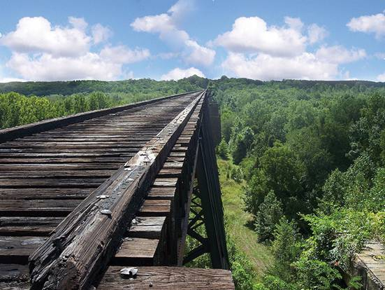 """The original High Bridge was constructed in 1853 and played a significant role in General Lee's retreat during the Civil War. During the Battle of High Bridge on April 7, 1865, the original bridge was partially burned by Confederate Troops. The current bridge was completed in 1914 and is the longest recreational bridge in the Virginia. The 2,400 foot long bridge sits 125 feet above the Appotmattox River and is part of a 31 mile shared-use trail built on Norfolk-Southern Railway right of way which was donated to the <a href=""""http://www.dcr.virginia.gov/"""">Virginia Department of Conservation and Recreation</a>. The trail permits biking, hiking, and horseback riding.   The restoration of the bridge received $743,000 in regular TE funding and an additional $2,000,000 in ARRA funding through the TE program. The funding paid for re-decking the entire bridge and constructing overlooks with steel canopies. More than 330,000 screws, 13,000 bolts of various sizes, and 1,065 railroad ties were used to renovate the bridge.  The contractor for the project was <a href=""""http://www.kbc-inc-va.com/"""">Keith Barber Construction, Inc</a>.   The 1,108 acre park runs through Appomattox, Nottoway, Cumberland, and Prince Edward counties. The trail also connects 4 other TE projects together. The Burkeville Station, Pamplin Station, and Farmville Depot are located along the trail and were all restored and rehabilitated with TE funding. Farmville also has a successful streetscape project near Longwood University. There is still work to be done on the trail but DCR has money set-aside to finish the terrific park. <a href=""""http://www.youtube.com/watch?v=Pt2w0MypNxs"""">To see video of the park, click here!</a>"""