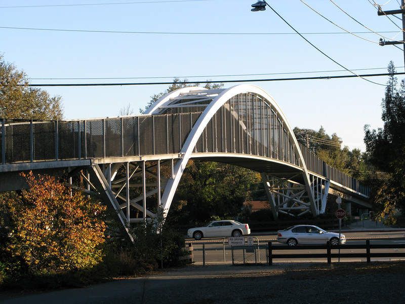 <b>This bridge over Ygnacio Valley Road prevents crossing conflicts between trail users and auto traffic.</b>  The Iron Horse Regional Trail connects two counties and 12 cities along 33 miles of the Southern Pacific Railroad right-of-way.  Between 1997 and 2002, $3,107,000 in TE funds financed trail expansion and infrastructure, including under- and over-passes.  The Iron Horse Regional Trail is open to pedestrians, bicyclists, and equestrians.  The trail is a popular route for commuters as well as school children.  It is convenient to a Bay Area Rapid Transit (BART) station, bus stops, and park-and-ride facilities.  The trail passes through commercial areas that have benefited from the establishment of the trail.  Restaurants, ice cream parlors, and bicycle and sporting goods stores have specifically located themselves alongside the trail.  Many businesses now include bicycle parking in support of the trail.  The Iron Horse Regional Trail provides thousands of citizens an alternative way to travel while serving as a linear park and greenway providing habitat for wildlife.