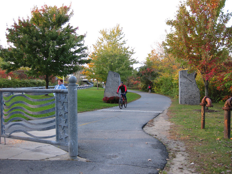 "One $48,000 TE grant in 1995 funded this artistic gate and the rock sculptures in the background at the trailhead in Cambridge.  The <a href=""http://www.minutemanbikeway.org"">Minuteman Bikeway</a> is an 11-mile rail-trail that connects Cambridge with Bedford, passing through Lexington and Arlington. This project converted an abandoned railroad, which provided passenger and freight service from 1846 to 1981 (Passenger service discontinued in 1977), into a multi-use bikeway. Over $2 million in federal TE funds were awarded to four projects that leveraged a total local match of nearly $530,000 to construct portions of the trail.   Connecting to the Alewife T Station in Cambridge, this bikeway serves as a regional connector providing pedestrians and bicyclists with access to subway and bus service. In addition, plowing in the winter makes the rail-trail accessible year-round. The Rails-to-Trails Conservancy inducted the Minuteman Bikeway into the national <a href=""http://www.railstotrails.org/ourWork/promotingTrailUse/trailRecognition/hallOfFame/index.html"">Rails-Trail Hall of Fame</a> in 2008. An interactive Google Map is available <a href=""http://maps.google.com/maps/ms?msa=0&msid=109226583957077835668.000465e72b5c80776ecd6&cd=20&geocode=FdjhgwIdyKe_-w&sll=41.524545,-73.895818&sspn=2.569111,6.049236&hl=en&ie=UTF8&ll=42.440434,-71.218529&spn=0.176595,0.308647&z=12"">here</a>."