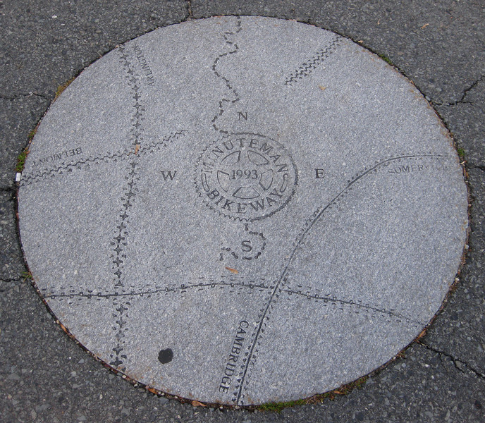 """Distinctive features along the trail, such as this placard, helps to define a sense of place for the communities through which it passes.   The <a href=""""http://www.minutemanbikeway.org"""">Minuteman Bikeway</a> is an 11-mile rail-trail that connects Cambridge with Bedford, passing through Lexington and Arlington. This project converted an abandoned railroad, which provided passenger and freight service from 1846 to 1981 (Passenger service discontinued in 1977), into a multi-use bikeway. Over $2 million in federal TE funds were awarded to four projects that leveraged a total local match of nearly $530,000 to construct portions of the trail.   Connecting to the Alewife T Station in Cambridge, this bikeway serves as a regional connector providing pedestrians and bicyclists with access to subway and bus service. In addition, plowing in the winter makes the rail-trail accessible year-round. The Rails-to-Trails Conservancy inducted the Minuteman Bikeway into the national <a href=""""http://www.railstotrails.org/ourWork/promotingTrailUse/trailRecognition/hallOfFame/index.html"""">Rails-Trail Hall of Fame</a> in 2008. An interactive Google Map is available <a href=""""http://maps.google.com/maps/ms?msa=0&msid=109226583957077835668.000465e72b5c80776ecd6&cd=20&geocode=FdjhgwIdyKe_-w&sll=41.524545,-73.895818&sspn=2.569111,6.049236&hl=en&ie=UTF8&ll=42.440434,-71.218529&spn=0.176595,0.308647&z=12"""">here</a>."""