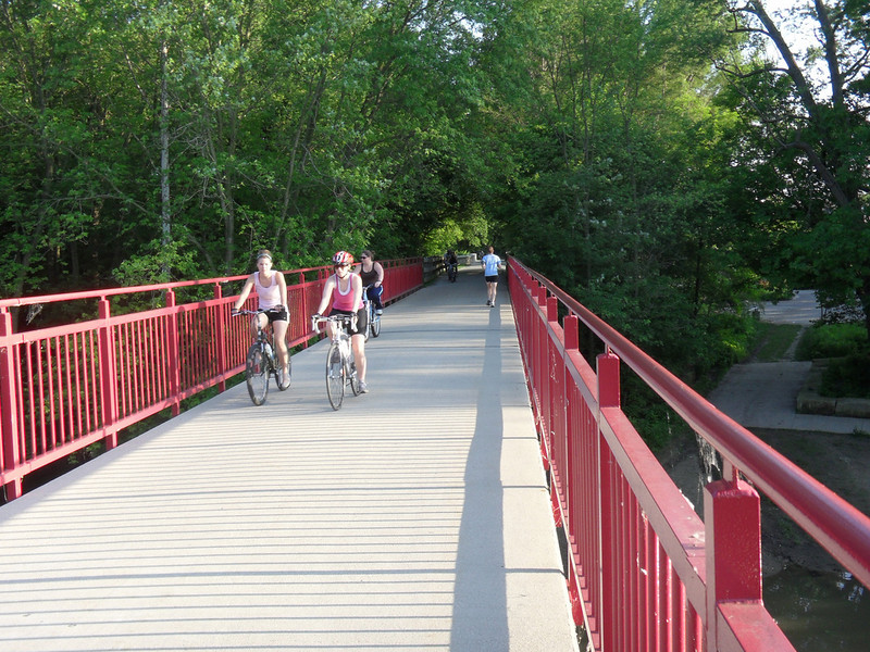 """<a href=""""http://www.flickr.com/photos/walkingsf/5460263838/sizes/l/in/photostream/"""">Photo Credit</a>  The Monon Trail or Monon Greenway as it is known locally is a 15.7 mile rail-trail stretching from Indianapolis to Carmel, Indiana. The trail sees about 1.3 million users a year and is a highly valued amenity among local citizens. Access to arts and entertainment is one of the highlights of the trail. The Indianapolis Art Center in Broad Ripple Village, Marott Park and Nature Preserve, Indiana State Fairgrounds, and the brand new Palladium at the Center for Performing Arts in Carmel are all easily accessible from the trail. Federal investment in the trail totals nearly $7,000,000 and has been matched by close to $4,700,000 in local funds. The asphalt trail connects many communities throughout the region and has been a significant economic boost for the local economy."""