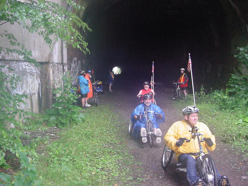 "Photo by Jim Holden.<br /> <br /> The Allegheny Valley Trails Association (AVTA) cleared out their area's local stock of used tires and started shipping in more, in order restore the historic Sandy Creek Tunnel, which was first built in 1907. The saga began in 1991, when AVTA accepted a donation of 19 miles of the Jamestown, Franklin & Clearfield Railroad (J, F&C), which included the crumbling tunnel. The Sandy Creek bicycle/pedestrian trail was developed on either side of the tunnel, leaving an unsafe passage for the many pedestrians and cyclists passing through it each day. AVTA developed some solutions to fix the tunnel, but came up against budgetary problems, and also had to meet conditions attached to its ""historic structure"" status, deemed by the Pennsylvania Historic and Museum Commission. So, AVTA turned to used tires, and cut the cost down to $2,000,000, including $803,000 in TE funds.<br /> <br /> Beginning in March 2005, workers began constructing a new 13-by-12 foot concrete tunnel inside the existing 30-by-30 foot one. Old tires were placed between the two tunnels to create a liner or cushion, protecting the inner tunnel. Jim Holden, president of the AVTA, credits Wexford Consulting Group of Wexford, Frank B. Taylor Engineering of New Castle and Shingledecker's Welding Inc. for making the concept a reality. ""It's quite a project,"" he said. ""It draws attention to the beneficial reuse of tires."" Holden estimates that about 250,000 tires were reused in the project.<br /> <br /> The Sandy Creek Tunnel, which is also known as Mays Mills Tunnel or Deep Valley Tunnel, was honored by Rails-to-Trails Conservancy (RTC) and the American Society of Landscape Architects in the category of Innovative Designs that Address a Particularly Difficult Challenge."
