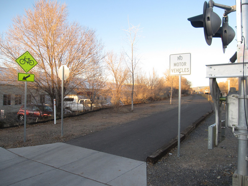 """Railroad crossings are treated in a variety of ways along the rail-trail. In more dense areas, a light, bell, and gate warn bicyclists and pedestrians of train traffic.   The <a href=""""http://www.railyardsantafe.com/rails-and-trails.php"""">Santa Fe Rail Trail</a>, which begins at Rabbit Road in Santa Fe and terminates in Lamy, runs adjacent to the <a href=""""http://www.nmrailrunner.com"""">Rail Runner Express commuter train</a> and <a href=""""http://sfsr.com/about.html"""">Santa Fe Southern Railway</a>, a 120 year old spur. The 11.5 mile rail-trail is a mix of pavement and dirt and was funded through a variety of public sources as well as private donations raised by the Santa Fe Conservation Trust. Specifically, the rail-trail received three separate TE grants in 1998 and 2005 amounting to $999,750 leveraging a local match of $333,250. Walkers, joggers, mountain bicyclists, and equestrians enjoy this community treasure."""