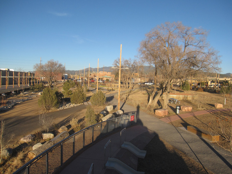 """The Santa Fe Railyard, pictured here, is a 13-acre community park located at the Sante Fe Depot. Funding for the park was managed by the Trust for Public Land. The park is part of a larger mixed-use development.  The <a href=""""http://www.railyardsantafe.com/rails-and-trails.php"""">Santa Fe Rail Trail</a>, which begins at Rabbit Road in Santa Fe and terminates in Lamy, runs adjacent to the <a href=""""http://www.nmrailrunner.com"""">Rail Runner Express commuter train</a> and <a href=""""http://sfsr.com/about.html"""">Santa Fe Southern Railway</a>, a 120 year old spur. The 11.5 mile rail-trail is a mix of pavement and dirt and was funded through a variety of public sources as well as private donations raised by the Santa Fe Conservation Trust. Specifically, the rail-trail received three separate TE grants in 1998 and 2005 amounting to $999,750 leveraging a local match of $333,250. Walkers, joggers, mountain bicyclists, and equestrians enjoy this community treasure."""