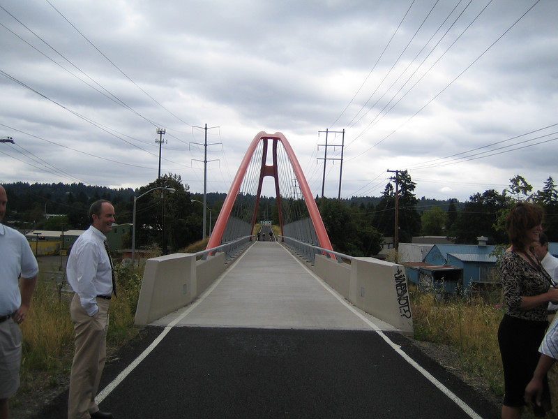 This project extends the Springwater trail, a multi-use path on an abandoned railroad line, over McLoughlin Boulevard, the Union Pacific Railroad, and Johnson Creek with the construction of three major bridges. Each bridge was designed to respond to the feature it is crossing. The suspension arch bridge over McLoughlin Boulevard also doubles as a gateway to the community both because of its shape and color. Awarded TE funds in 2003, the project was completed in the fall of 2006. Federal Share $4,209,233.00 Match $481,767 Total $4,691,000