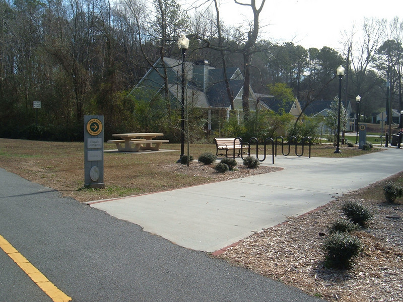 """Access point to Silver Comet Trail from nearby housing development<br /> <br /> The Silver Comet Trail, one of the most popular spots in northwest Georgia for outdoor recreation and bicycle commuting, sprouted from an abandoned rail corridor between Atlanta and the Alabama state line. In the early 1990s, a group of private citizens and non-profit organizations, including the PATH Foundation and the Georgia Rails to Trails Society, spearheaded the development of the trail, working with the Georgia Department of Transportation (GDOT), the Georgia Department of Natural Resources and the three counties adjacent to the trail: Cobb, Paulding and Polk. GDOT purchased the 57-mile corridor in 1992 from CSX for $5.8 million. Today, the trail passes through three Georgia counties and connects with the Chief Ladiga Trail in Cleburne County, Alabama.  These two trails combined run over 100 miles and form the longest paved trail in the United States.<br /> <br /> Development of the Silver Comet Trail was supported by TE grants in 1998 ($695,000 with a $173,750 local match from the City of Rockmart), 2000 ($400,000 with a $202,840 local match from the Cobb County DOT; $50,000 with a $12,500 local match from the Paulding County Chamber of Commerce; and $959,000 with a $239,750 local match from Polk County),  2001 ($875,000 with a $343,200 local match from GDOT), and 2004 ($750,000 with a local match of $187,500 from the Cobb County DOT).  The grants and matches total $4,888,540.<br /> <br /> Learn more about The Silver Comet Trail at <a href=""""http://www.silvercometga.com/"""">http://www.silvercometga.com/</a> and <a href=""""http://www.silvercomet.org/"""">http://www.silvercomet.org/</a>."""