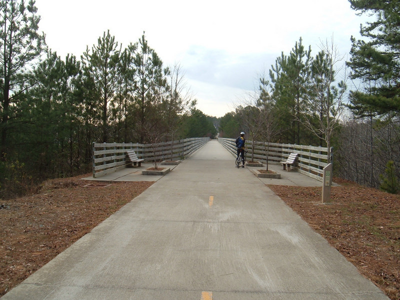 "Bridge on the Silver Comet Trail<br /> <br /> The Silver Comet Trail, one of the most popular spots in northwest Georgia for outdoor recreation and bicycle commuting, sprouted from an abandoned rail corridor between Atlanta and the Alabama state line. In the early 1990s, a group of private citizens and non-profit organizations, including the PATH Foundation and the Georgia Rails to Trails Society, spearheaded the development of the trail, working with the Georgia Department of Transportation (GDOT), the Georgia Department of Natural Resources and the three counties adjacent to the trail: Cobb, Paulding and Polk. GDOT purchased the 57-mile corridor in 1992 from CSX for $5.8 million. Today, the trail passes through three Georgia counties and connects with the Chief Ladiga Trail in Cleburne County, Alabama.  These two trails combined run over 100 miles and form the longest paved trail in the United States.<br /> <br /> Development of the Silver Comet Trail was supported by TE grants in 1998 ($695,000 with a $173,750 local match from the City of Rockmart), 2000 ($400,000 with a $202,840 local match from the Cobb County DOT; $50,000 with a $12,500 local match from the Paulding County Chamber of Commerce; and $959,000 with a $239,750 local match from Polk County),  2001 ($875,000 with a $343,200 local match from GDOT), and 2004 ($750,000 with a local match of $187,500 from the Cobb County DOT).  The grants and matches total $4,888,540.<br /> <br /> Learn more about The Silver Comet Trail at <a href=""http://www.silvercometga.com/"">http://www.silvercometga.com/</a> and <a href=""http://www.silvercomet.org/"">http://www.silvercomet.org/</a>."