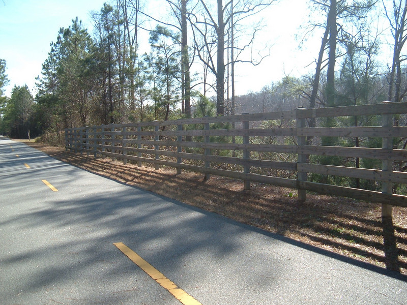 "Fencing along the Silver Comet Trail<br /> <br /> The Silver Comet Trail, one of the most popular spots in northwest Georgia for outdoor recreation and bicycle commuting, sprouted from an abandoned rail corridor between Atlanta and the Alabama state line. In the early 1990s, a group of private citizens and non-profit organizations, including the PATH Foundation and the Georgia Rails to Trails Society, spearheaded the development of the trail, working with the Georgia Department of Transportation (GDOT), the Georgia Department of Natural Resources and the three counties adjacent to the trail: Cobb, Paulding and Polk. GDOT purchased the 57-mile corridor in 1992 from CSX for $5.8 million. Today, the trail passes through three Georgia counties and connects with the Chief Ladiga Trail in Cleburne County, Alabama.  These two trails combined run over 100 miles and form the longest paved trail in the United States.<br /> <br /> Development of the Silver Comet Trail was supported by TE grants in 1998 ($695,000 with a $173,750 local match from the City of Rockmart), 2000 ($400,000 with a $202,840 local match from the Cobb County DOT; $50,000 with a $12,500 local match from the Paulding County Chamber of Commerce; and $959,000 with a $239,750 local match from Polk County),  2001 ($875,000 with a $343,200 local match from GDOT), and 2004 ($750,000 with a local match of $187,500 from the Cobb County DOT).  The grants and matches total $4,888,540.<br /> <br /> Learn more about The Silver Comet Trail at <a href=""http://www.silvercometga.com/"">http://www.silvercometga.com/</a> and <a href=""http://www.silvercomet.org/"">http://www.silvercomet.org/</a>."
