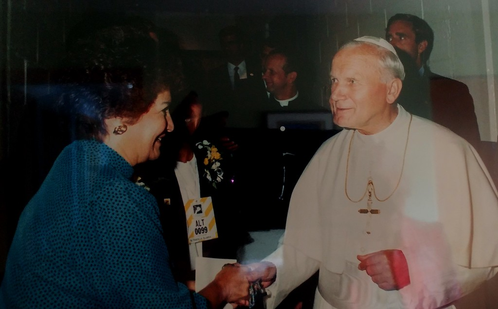 . Joyce Frias, 84 of White Lake,  secretary for the late Father William Easton of St. Vincent de Paul Catholic Church during the visit, accepts a rosary from Pope Saint John Paul II. Photo Courtesy of Joyce Frias