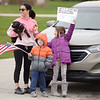 From left, LeAne, Jace and Anistynn Warrum watch as teachers from East Elementary parade through their students' neighborhoods to encourage them on what would have been their first day back after spring break on Monday.