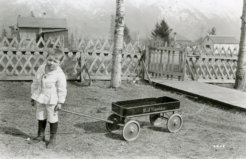 Ferde Greene Photo<br /> 3/27/1925 Allan 4years Old, Ed Bryant Taxidermy who shot and mountain goats for GN Railroad worked in the building on the left.  Ed was an actor who came from the east.<br /> 1402