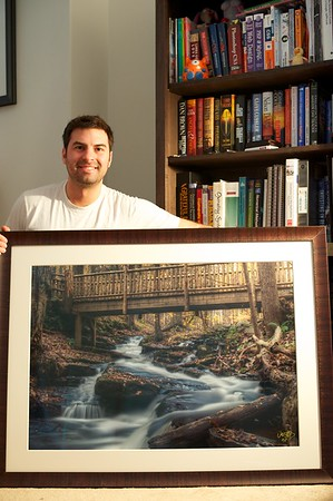 Thomas M Thurston crouches beside a 24x36 artist proof of Autumn Waters.