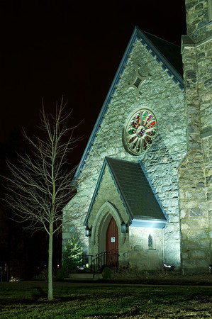 A churches exterior is prominently displayed at night with flood lights hightlighting the front door and surroundings.
