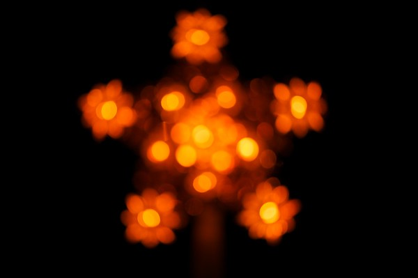 A Christmas tree star topper is photographed while out-of-focus to create a beautiful golden flower abstract.